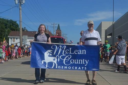 A man and woman marching in parade holding a banner for Democratic Party