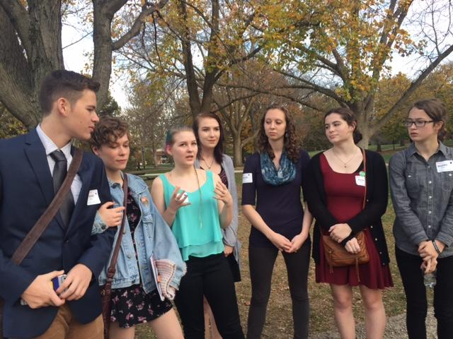 A group of students and their teacher standing outside the Humanity Summit at Illinois Wesleyan University
