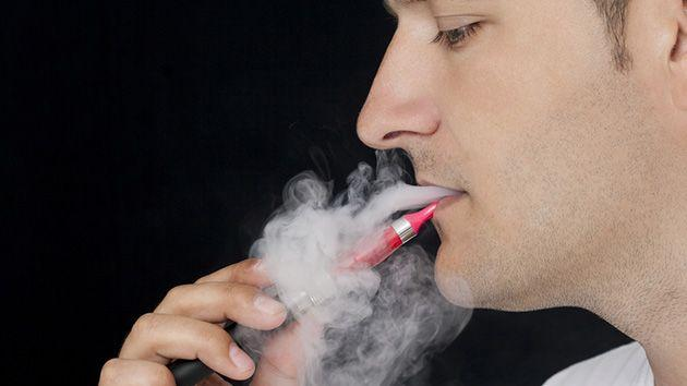 Man using an e-cigarette with vapor swirling around his face.