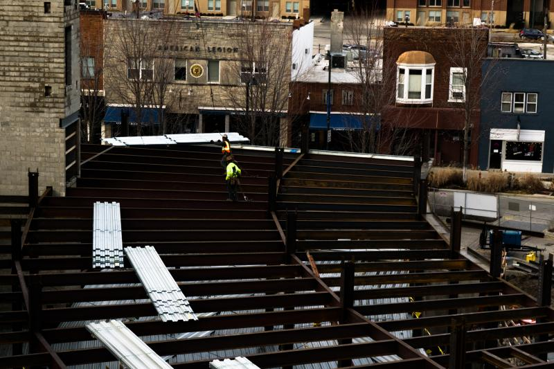 Workers walking steel beams at the One Uptown site.