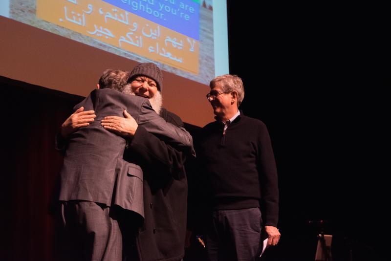 Town of Normal Mayor Chris Koos looks on as Bloomington Mayor Tari Renner Imam Abu-Emad Al-Talla embrace.
