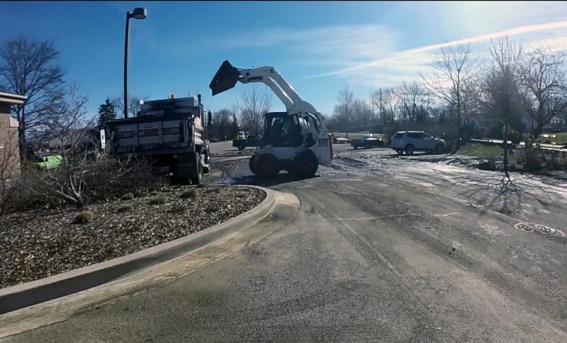 A Bobcat front end loader scrapes and dumps mud covering the parking lot of Epiphany Catholic Church and Schools.