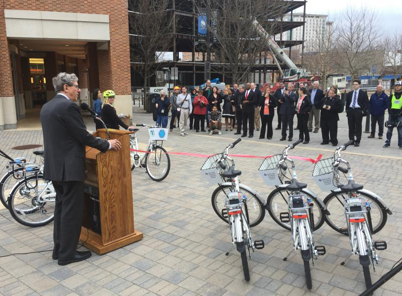Town of Normal Mayor Chris Koos address a crowd at Gateway Plaza in Uptown during the Bike Share 309 ribbon cutting ceremony.
