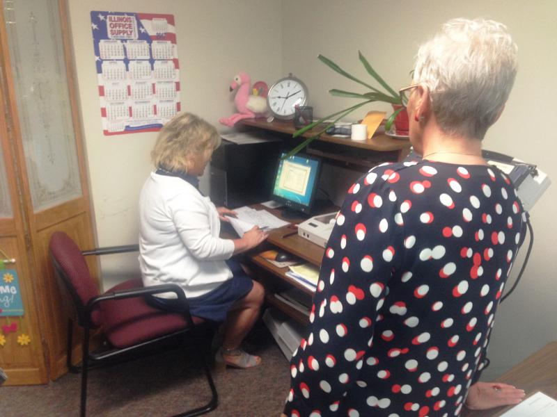 County Clerk election workers and a contractor go through ballot tabulation in the race for Mayor of Normal.