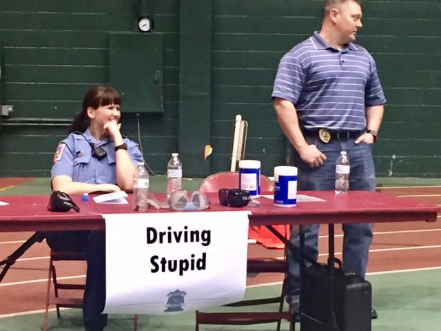 Two police officers at a table with a sign reading Driving Stupid