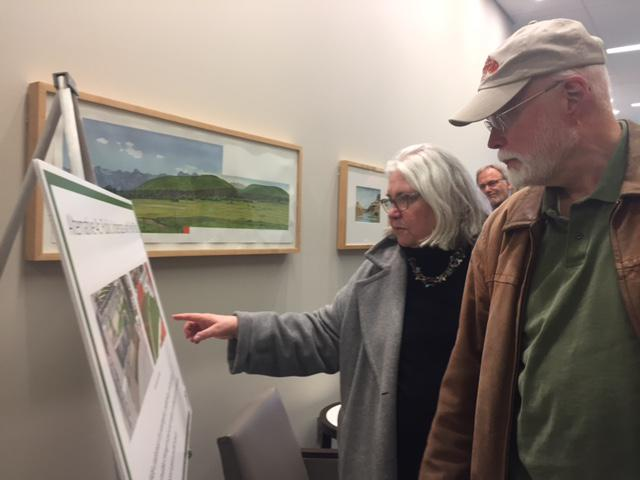 Man and woman look at architects drawings of an underpass and neighboring park.