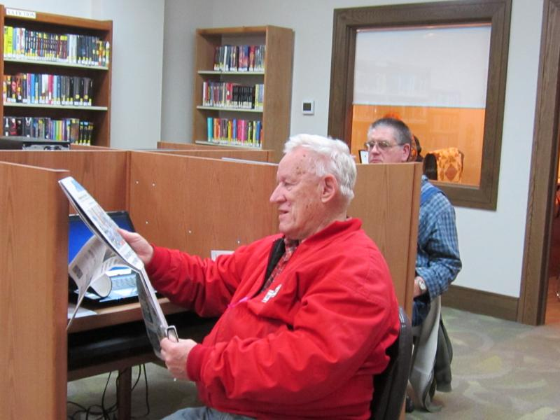 A patron reads the newspaper in one of Carlock Library's new reading sections.