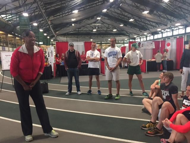 Olympic athlete inside Shirk Center with three athletes and a coach behind her