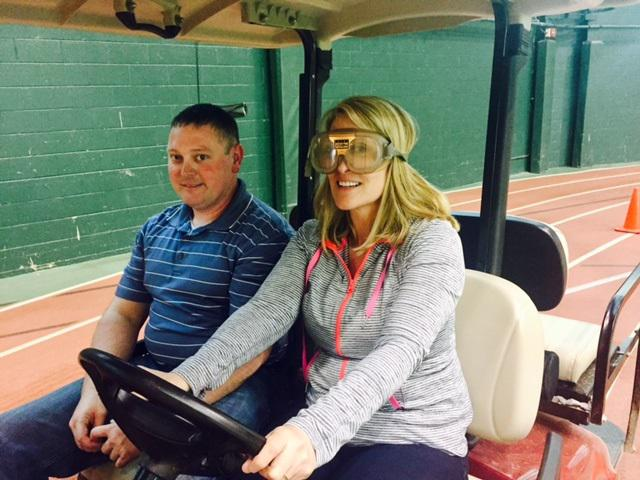 Man and woman wearing goggles driving a golf cart