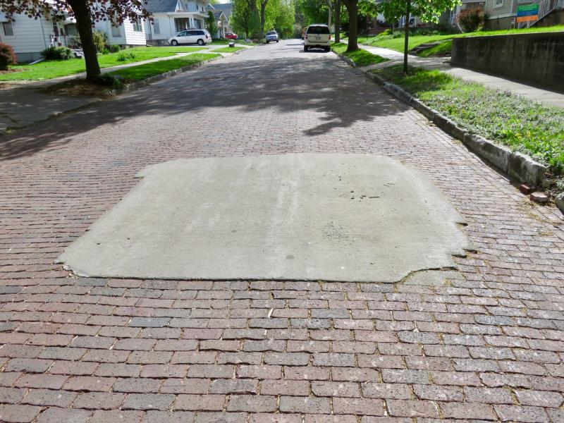 A cement patch on East Monroe St. The city will investigate repaving Monroe with bricks.