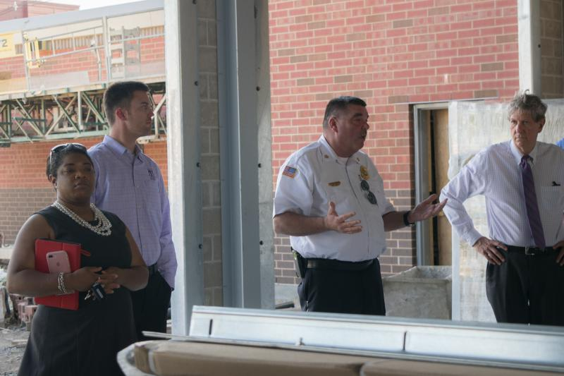 council members Chemberly Cummings and Scott Preston, and Mayor Chris Koos listen to fire chief Mick Humer as he explains the main garage of the new fire station in Normal on Osage St.
