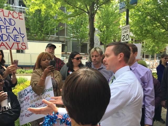 Republican Congressman Rodney Davis speaking to a crowd of protesters outside his Uptown Normal office.