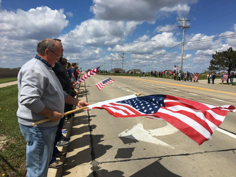 Supporter Lloyd Cook getting his flag ready for the funeral procession.