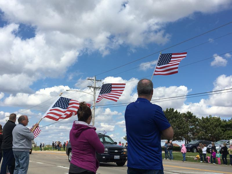 Supports lift flags in the air as the funeral procession passes by.