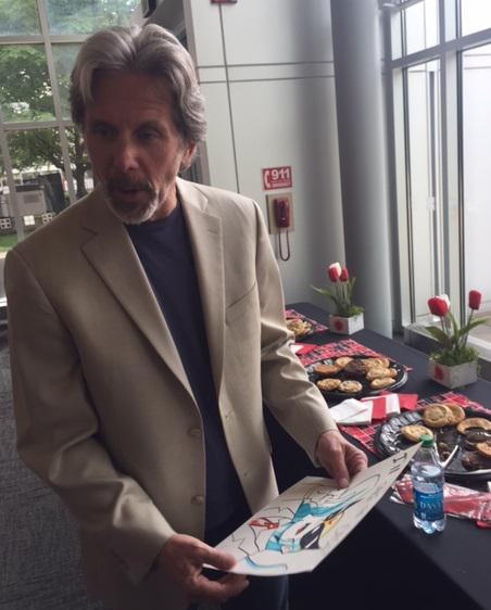 Actor Gary Cole holding cartoon drawing of one of his animated characters