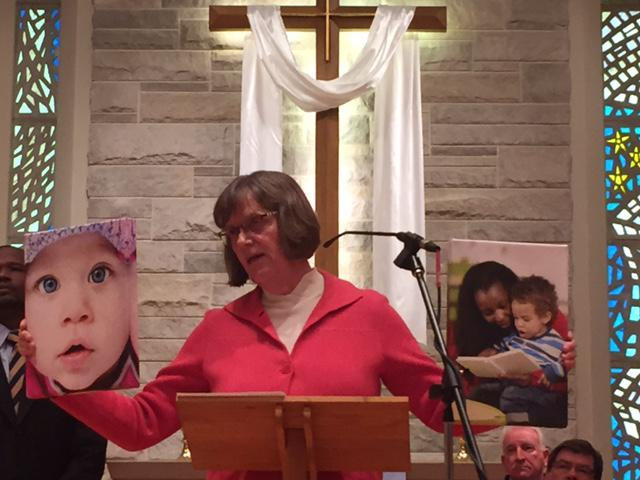 Woman at church podium holding a photo of children in each hand.