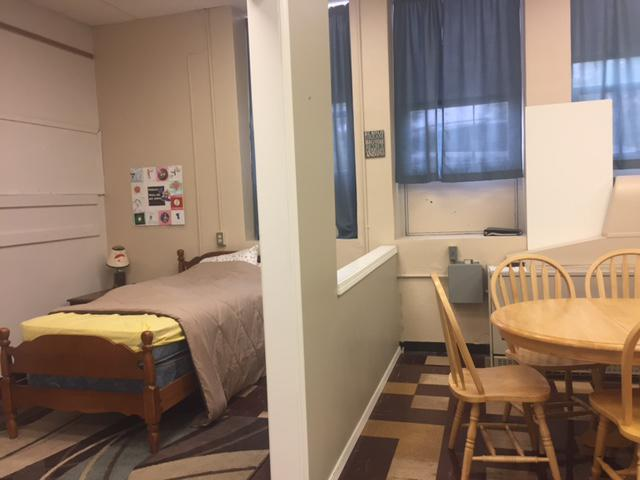 Bed and kitchen table in a room to help teach life skills to students with disabilities.