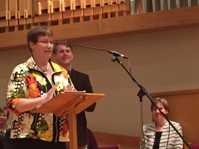 Woman at podium with back in background and woman sitting in a church pew stage left