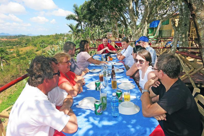 Several people at outdoor table eating a meal in Cuba.