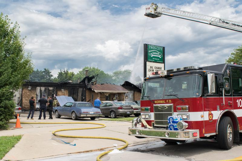 Firefighters calm the remaining fire at Twin City Auto Garage