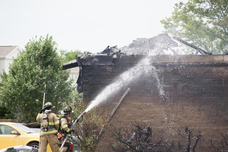 Firefighters tend to the roof of the garage shop