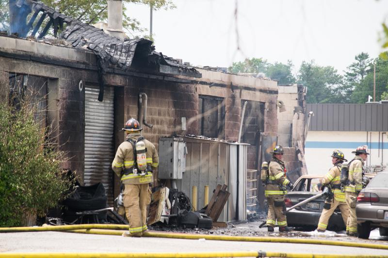 Firefighters tend to the vehicles and remaining parts around the North side of the building