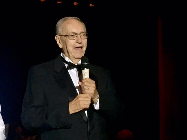 Man in a tux with a microphone in his hand.