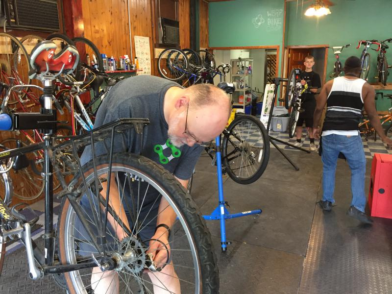 Friends of the Constitution Trail Board member and organizer of the bike co-op, Julian Westerhout, works on a bike on Saturday.