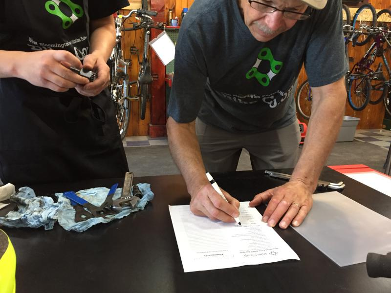 Dan Steadman (right), former Friends of the Constitution Trail President and Bike Coop organizer helps Colton Houck fill out volunteer paper work. Colton is volunteering toward acquring his own bike.