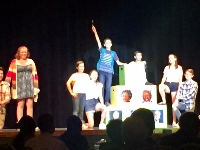Student perform a play on stage and stand on boxes with images of McLean Co History Makers.