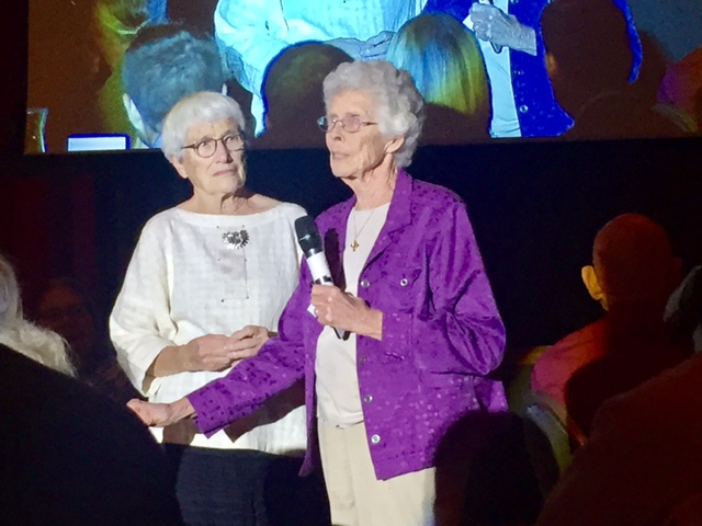 Two women with one holding a microphone.