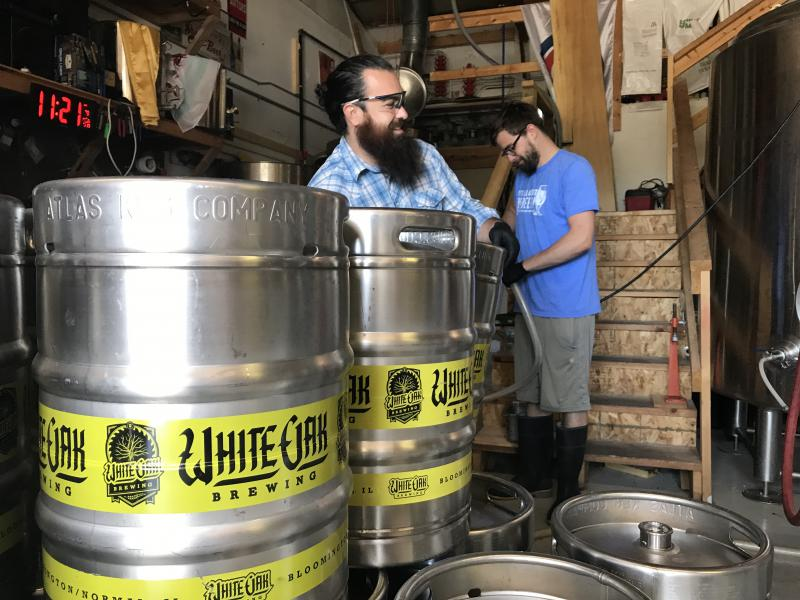 Bryan Ballard and Scott Scherer, two of three co-owners at White Oak Brewery, work in their production facility in west Normal.