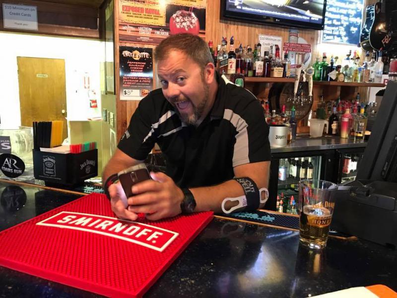 Man smiling behind a bar.