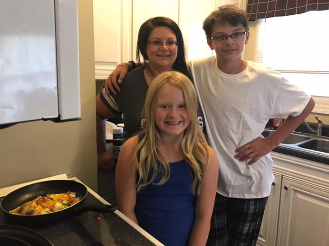 Woman and her son and a girl who is an actor in the movie standing in a kitchen next to a stove with an omlette in a pan.