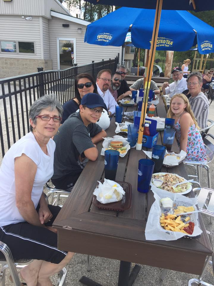 Actors seated outside at a picnic table at local eatery, enjoying a wrap dinner.