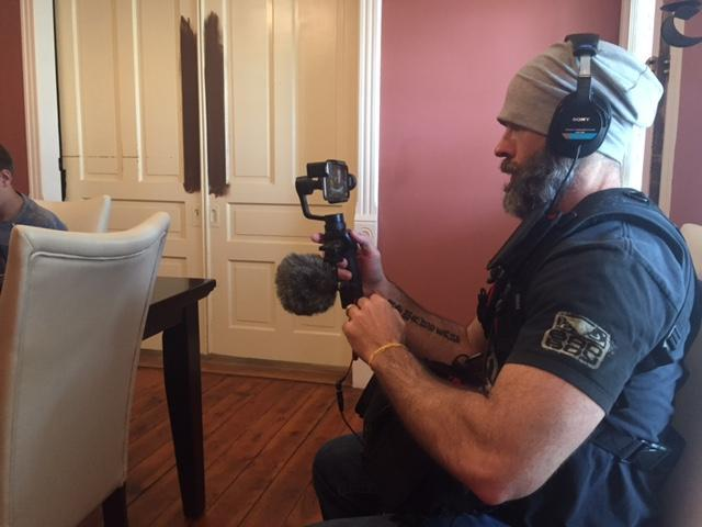 Man wearing headphones and camera while kneeling in a dining room.