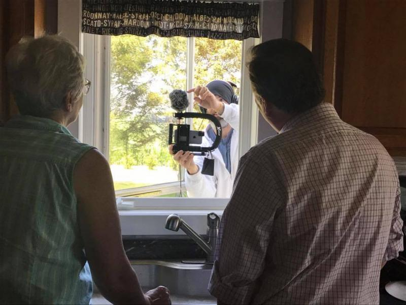 Camerman with camera shooting two actors through an open window.