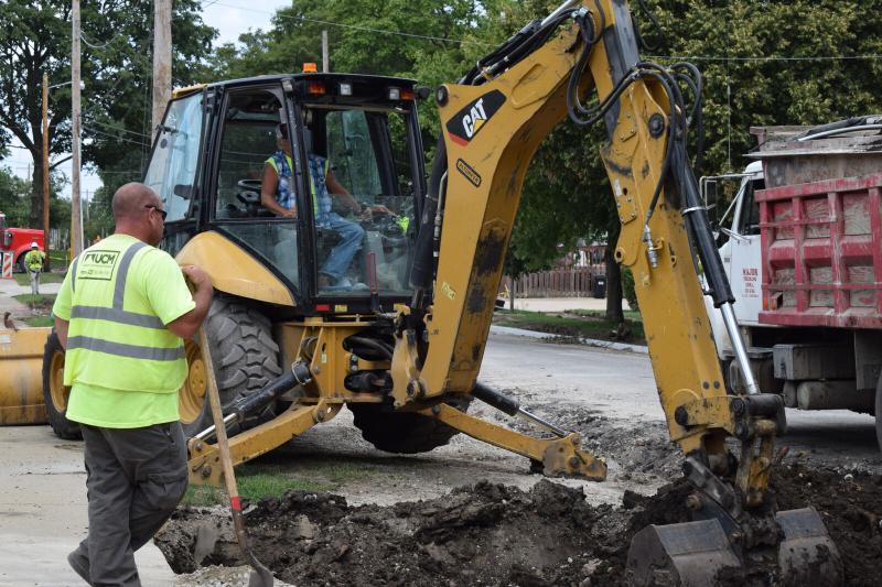 Pavement is dug out by man operating a large endloader.