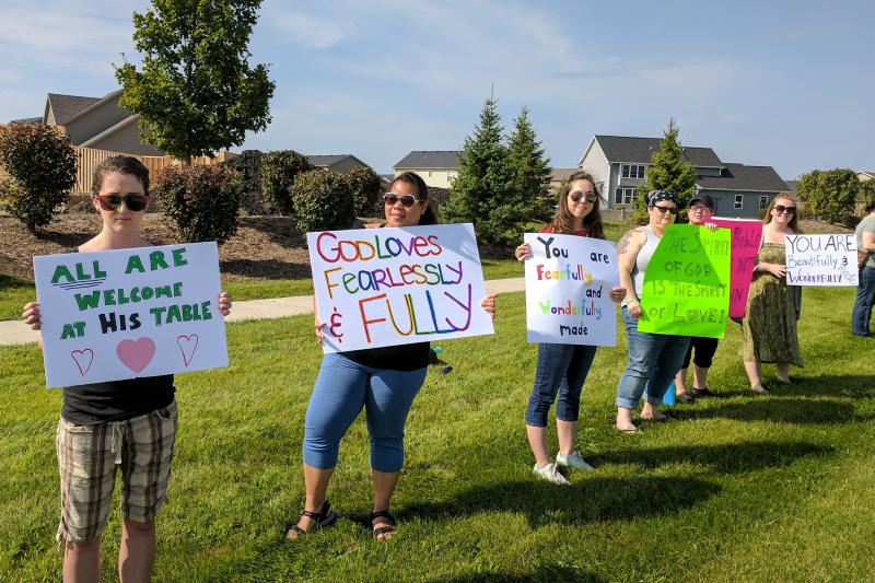 "Protesters from Humans for the Advancement of Religious Equality demonstrate across from Eastview Church."" Left to right are . Genevieve Pilon, Christy Mahrt, Katelyn Bright, Mandy Kampen, Angela Warner, and Bevin Choban."