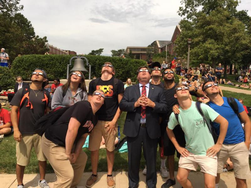 ISU President Larry Dietz gazes up at the eclipse with students on the Quad on Monday, Aug. 21, 2017.