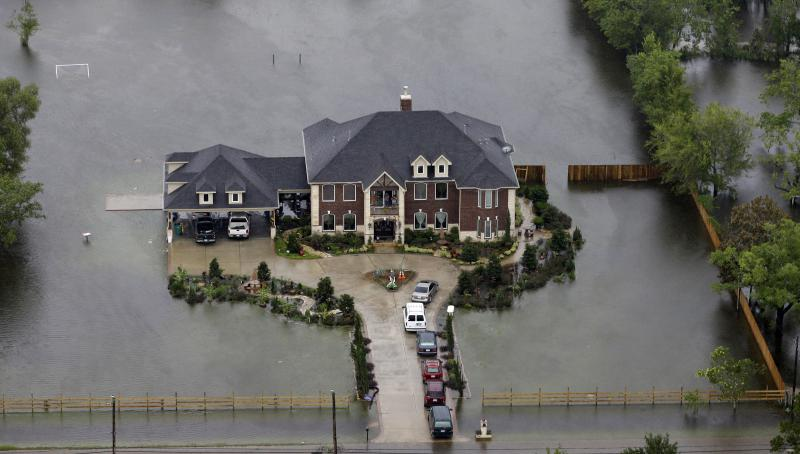 A home is surrounded by floodwaters from Tropical Storm Harvey on Tuesday, Aug. 29, 2017, in Houston.
