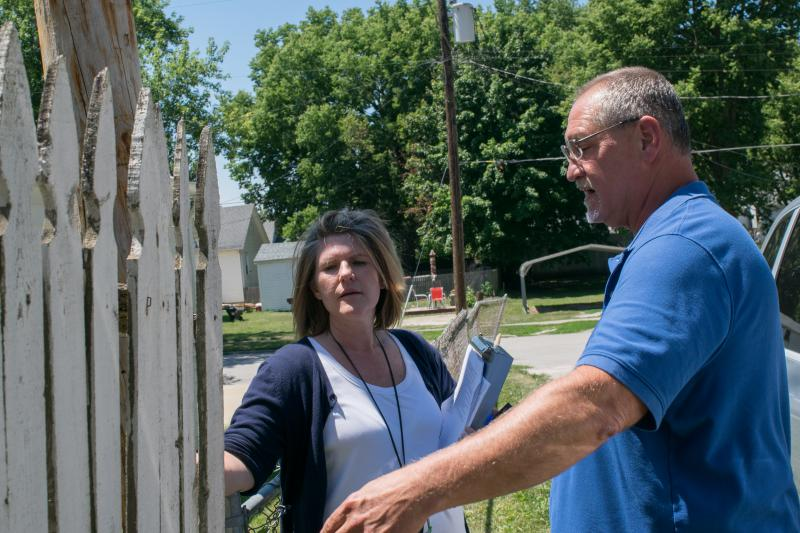 Gayle Price, left, one of Bloomington's two housing inspectors, checks a fence at a rental property with Carey Snedden, the city's manager for code enforcement, in summer 2017.