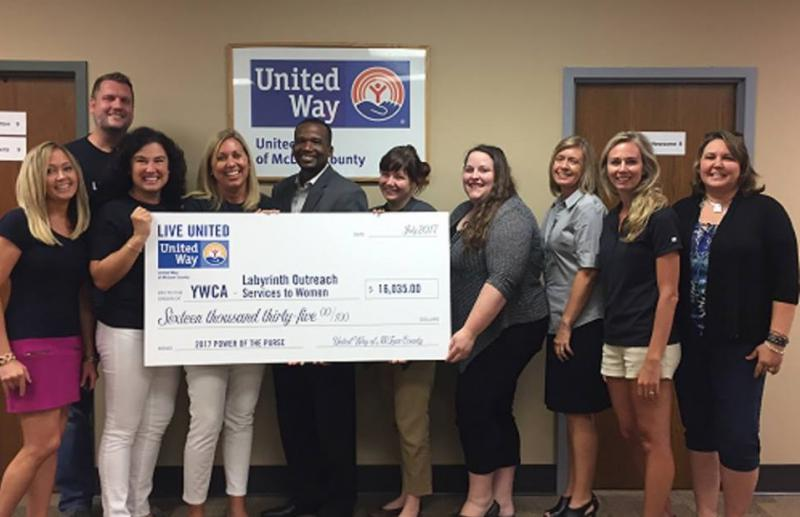 David Taylor with United Way of McLean County along with members of the 2nd annual Power of the Purse Committee presents the YWCA' s Labyrinth Outreach Services program with a donation.