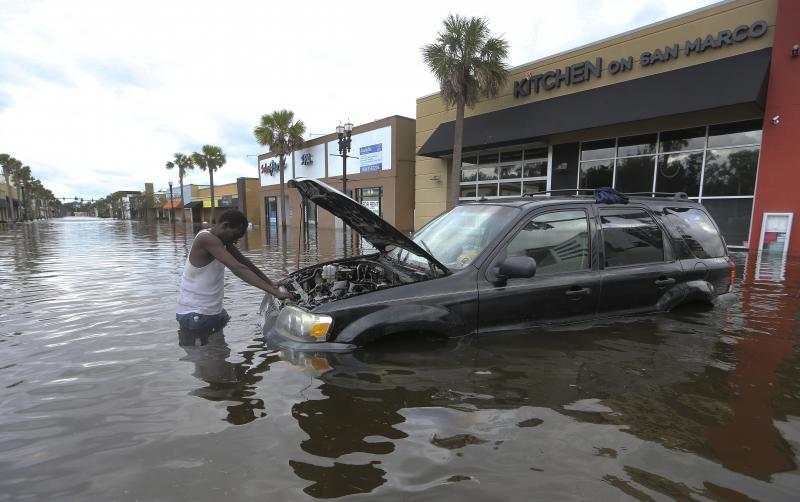 John Duke tries to figure out how to salvage his flooded vehicle in the wake Hurricane Irma, Monday, Sept. 11, 2017, in Jacksonville, Fla.