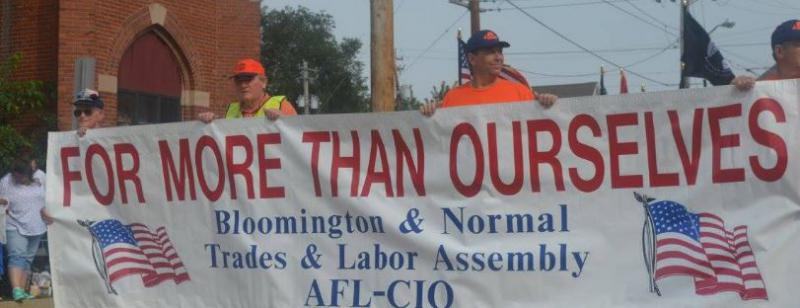 Men holding a sign marching in the Labor Day Parade in Bloomington