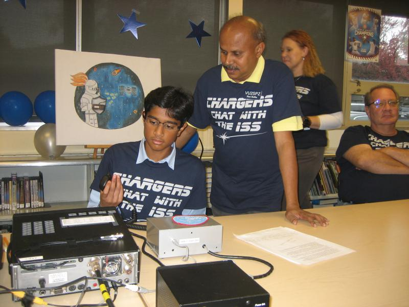 Dhruv Rebba, an eight grader at Chiddix Junior High, prepares to place a ham radio call to the International Space Station.  Beside him is his father, Hari, another ham radio enthusiast.