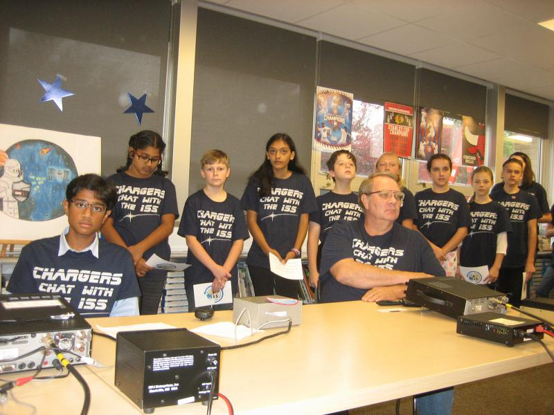 "Students from Chiddix Junion High, dressed in tee shirts with the school nickname ""Chargers,"" line up to ask questions of astronaut Joe Acabo who spoke from the International Space Station."