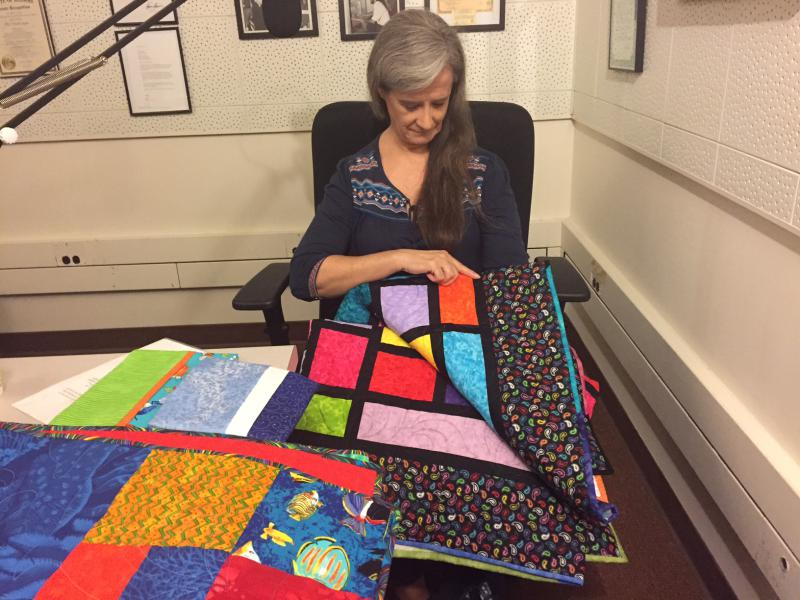Quilter Nancy Stone and the quilts going to the kids of the Bed Blitz.