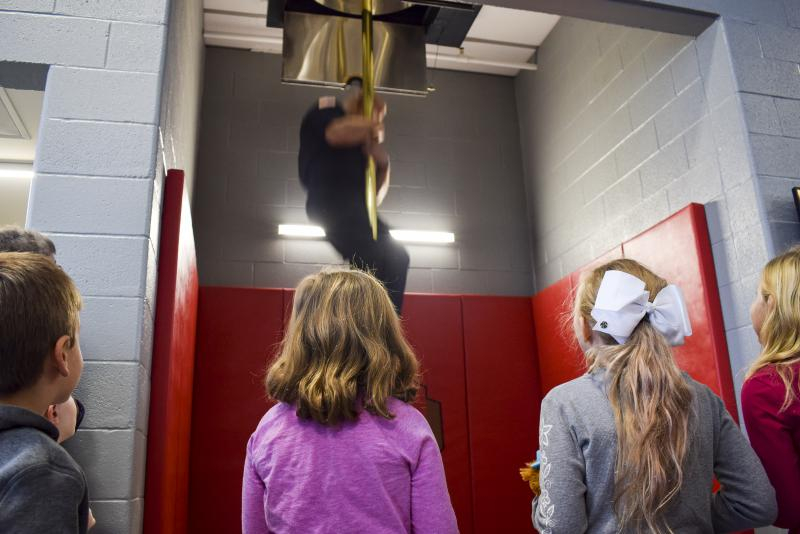 Children Watch A Firefighter Use the Fire Pole