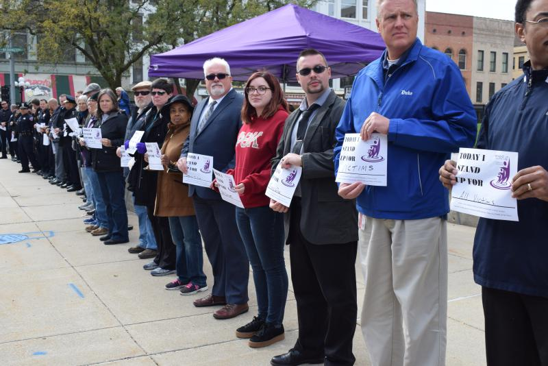 "A portion of the rally's crowd holds their customizable ""I Stand For..."" signs to show support for domestic violence victims in downtown Bloomington on Monday, Oct. 30, 2017."